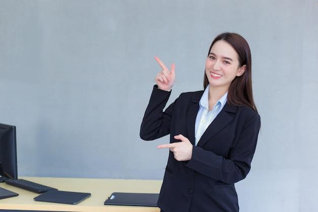 Азиатская профессиональная деловая женщина, которая носит черный костюм, стоит и показывает руку, чтобы что-то представить