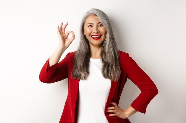 Азиатская профессиональная деловая женщина в красном пиджаке, показывая знак ок и улыбается, одобряет и любит что-то, стоя на белом фоне.