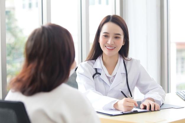 의료 코트를 입은 아시아 전문 의사 여성이 여성 환자와 대화