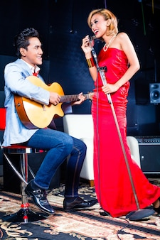Asian professional singer and guitarist recording new song or album cd in studio