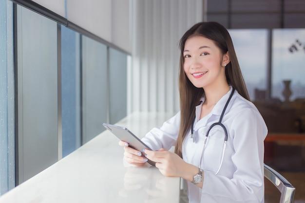 흰색 의료 코트를 입은 아시아 전문 여성 의사는 병원 도서관의 의자에 앉아 의료 개념의 치료를 위해 태블릿에서 일부 정보를 검색합니다.