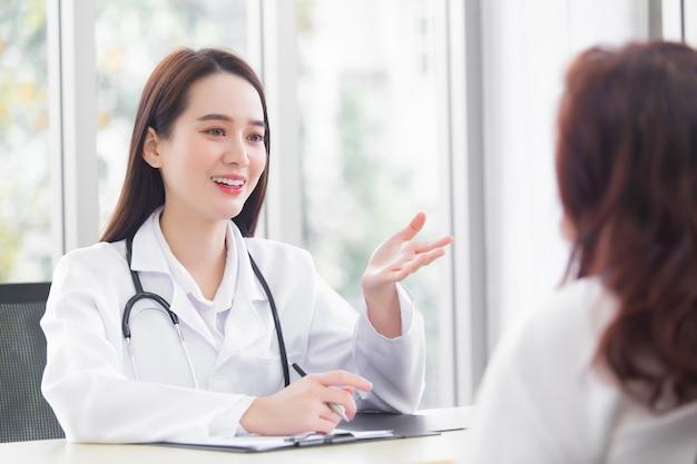 アジアの専門職の女性医師が患者の高齢者に医療ソリューションを提案