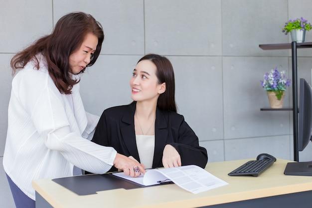 아시아 전문 여성이 직장 상사와 논의하기 위해 종이나 문서를 가리키고 있습니다