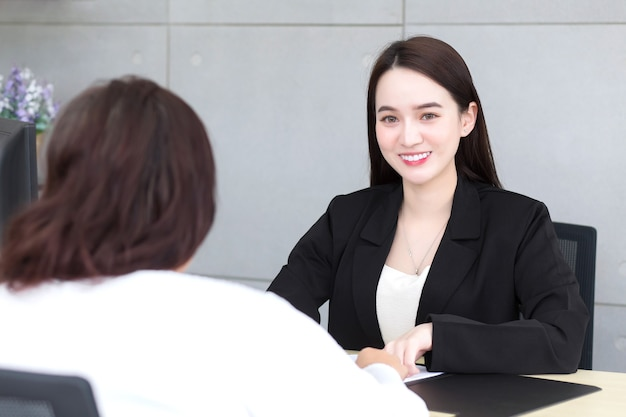 Asian professional woman is working and pointing on the paper or document to discuss with her boss at office.