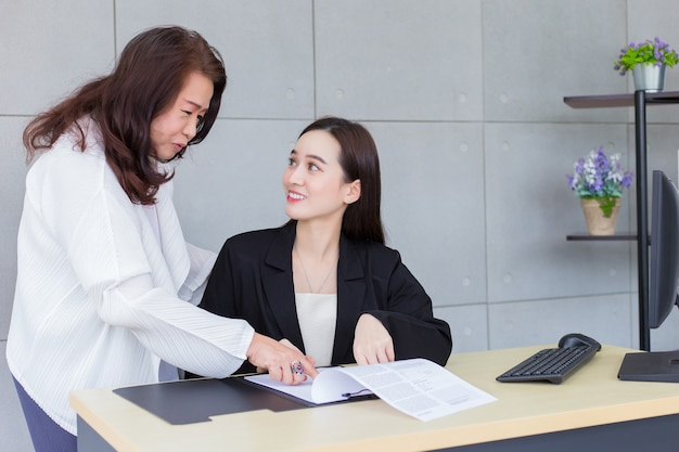 Asian professional woman is working and pointing on the paper or document to discuss with her boss