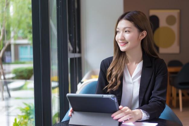 Азиатская профессиональная рабочая женщина в черном костюме работает над ipad или планшетом