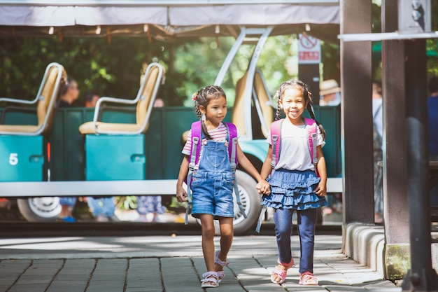 Asian pupil kids with backpack holding hand and going to school with school bus together