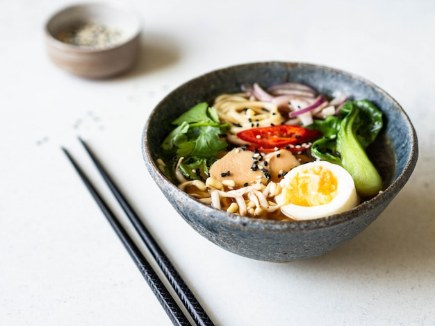Asian ramen noodles with chicken, pak choi cabbage and egg on grey background.