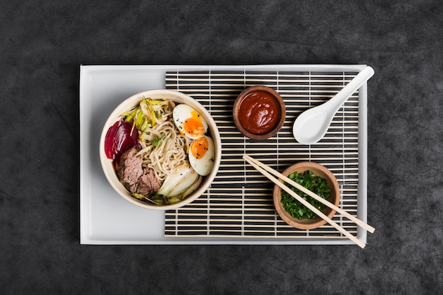 Asian ramen noodles with eggs; salad; sauce and chive on white tray against black texture backdrop