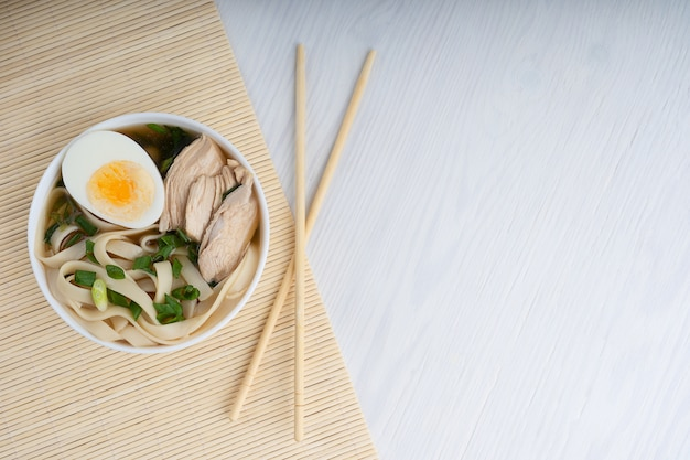 Asian ramen soup made of chicken broth with noodles decorated by halved egg and meat slices. top view