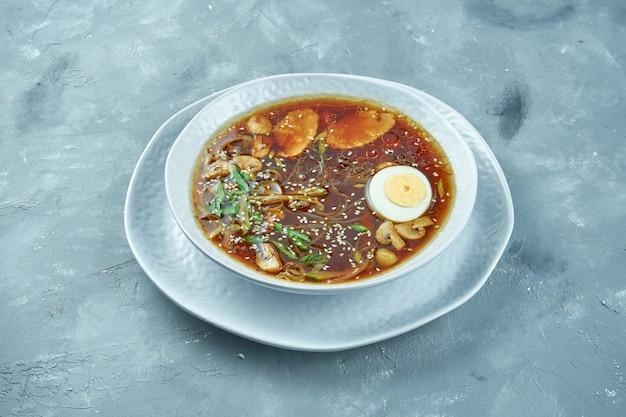 ゆで卵、麺、キノコ、鶏肉の白いボウルのアジアンラーメンスープ