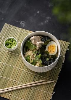 메뉴와 요리법이 있는 기사를 위해 어두운 카피스페이스 표면에 신선한 양파를 추가한 닭고기와 계란 국수를 곁들인 아시아 라면 수프