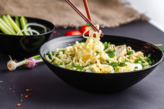 Asian ramen soup with chicken, egg, chives in black bowl on table. ramen noodles bowl