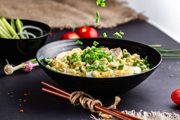 Asian ramen soup with chicken, egg, chives in black bowl