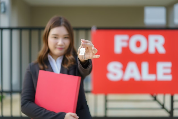 Asian real estate agent or realtor woman smiling and holding red file with showing house key in front of house.