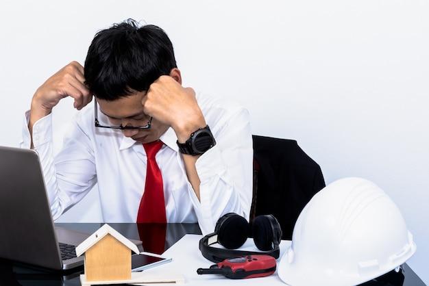 아시아 부동산 사업가는 흰색 배경을 가진 직장에서의 성공적인 판매로 스트레스를 받았습니다.