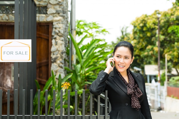 새 집을 제시하는 아시아 부동산 중개업자