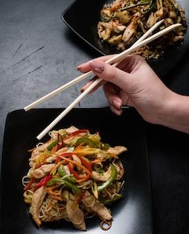 Ресторан азиатской кухни обслуживает. женщина ест курицу и овощной салат палочками для еды