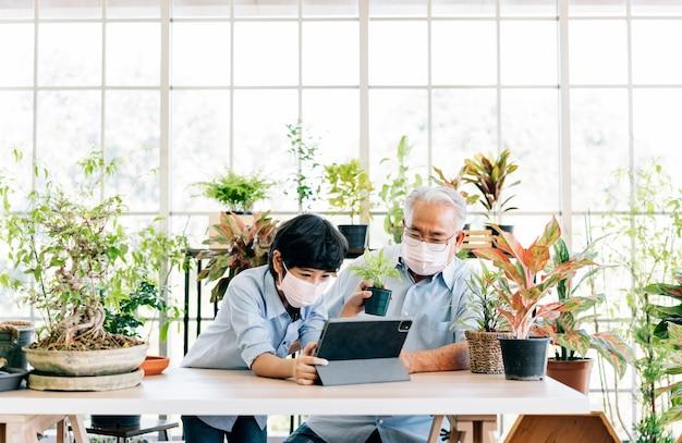 아시아의 은퇴한 할아버지와 손자는 마스크를 쓰고 즐겁게 태블릿으로 식물을 팔기 위해 살고 있습니다. 은퇴 취미와 라이프 스타일. 노인과 젊은이 사이의 가족 유대. 검역의 개념입니다.