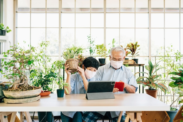 Asian retirement grandfather and grandson wearing a face mask and live to sell plants on a tablet with fun.