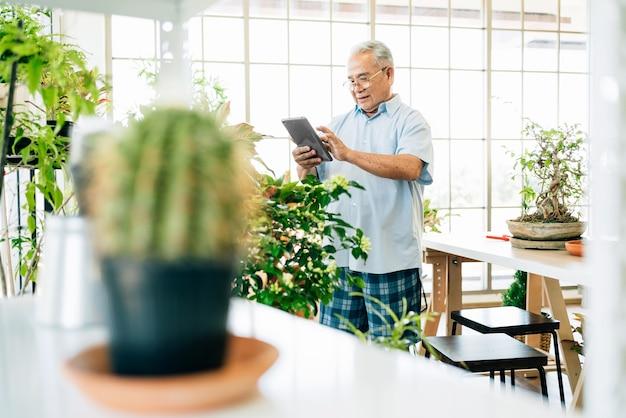 良質の植物をオンラインで販売するためにデジタルタブレットを使用しているアジアの引退祖父