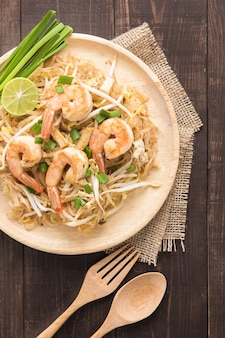 Asian rice noodles with shrimp and vegetables on wooden table.