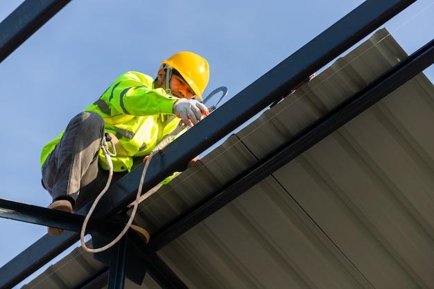 アジアの屋根の建設作業員は、屋根フレームを取り付けるための安全高さ装置を着用します。建設現場の安全ボディハーネス用フック付き作業員用の落下防止装置。