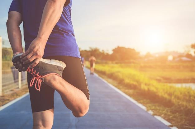 아시아 러너는 도로에서 달리기 전에 몸을 따뜻하게합니다.