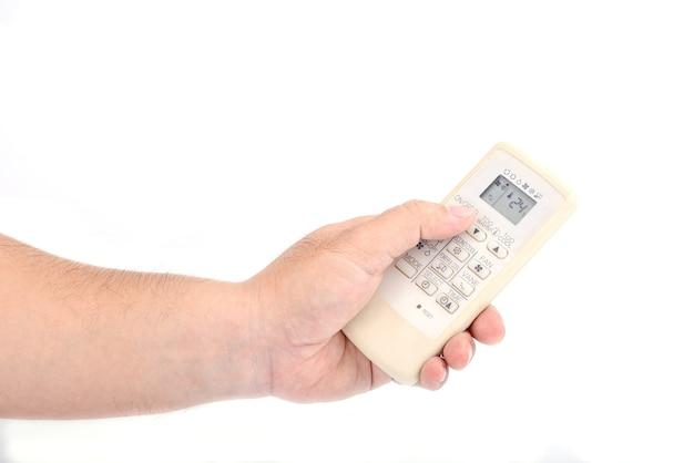 아시아인의 손은 흰색 배경에 격리된 열기, 닫기 또는 온도 조정을 위해 에어컨의 원격 제어를 들고 있습니다.