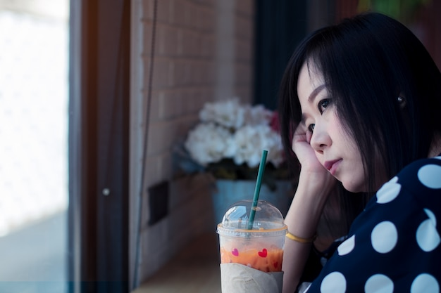 Asian sad woman near window thinking about something with loneliness