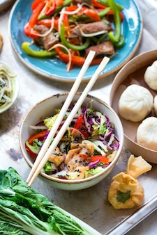 Asian salad with chicken stirfry, bok choy, cabbage and pepper, dim sum bowl, spring rolls