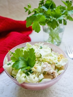 Asian salad with greens and cabbage on light background