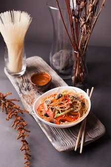 Asian salad with noodles and vegetables, sprinkled with sesame seeds with chopsticks on a wooden tray. asian cuisine, garnish, healthy food, vegetarian menu.