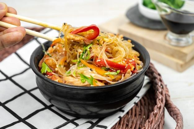 Азиатский салат с рисовой лапшой, овощами, грибами, курицей и соевым соусом. фунчоза с белой прозрачной лапшой в черной тарелке