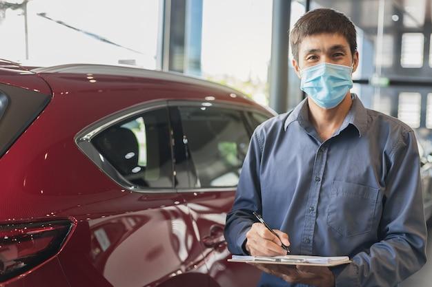 아시아 세일즈맨은 대리점의 차고에서 클립 보드에 쓰기 검사 검사에서 일하는 외과 마스크를 착용