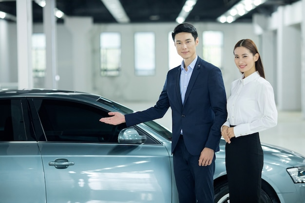 Asian salesman in auto business with saleswoman
