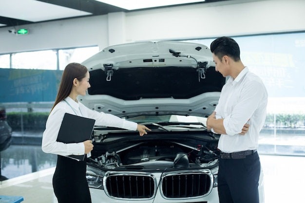 Asian saleswoman in auto business with man