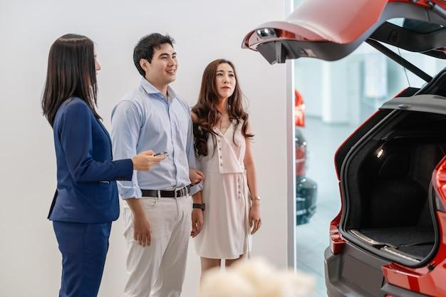 車のトランクについて車の機能をショールーム、カスタマーサービス、営業担当者のコンセプトでカップルの顧客に示すアジアのセールスウーマン