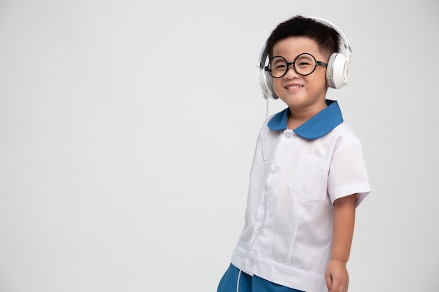 分離されたヘッドフォンで音楽を聴くアジアの学校の男の子
