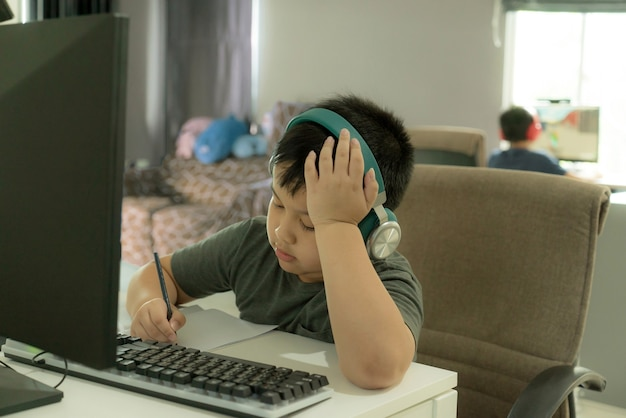 Asian school boy showing the boredom during online learning at homr boring home school