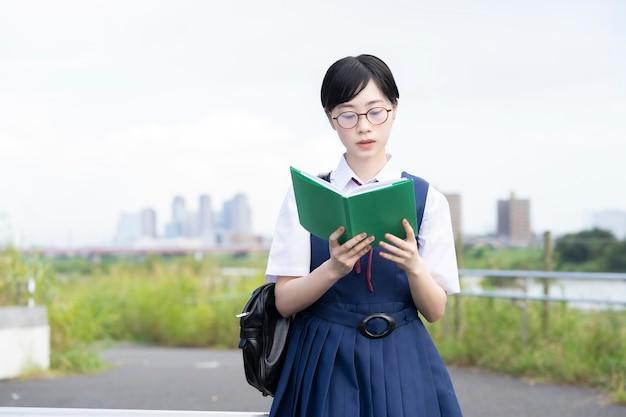 真面目な表情で本を読んでいるアジアの女子高生