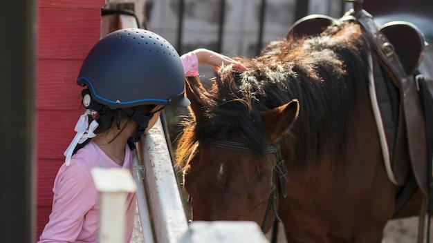 馬、乗馬、または馬の牧場での乗馬の練習をしているアジアの学校の子供の女の子。