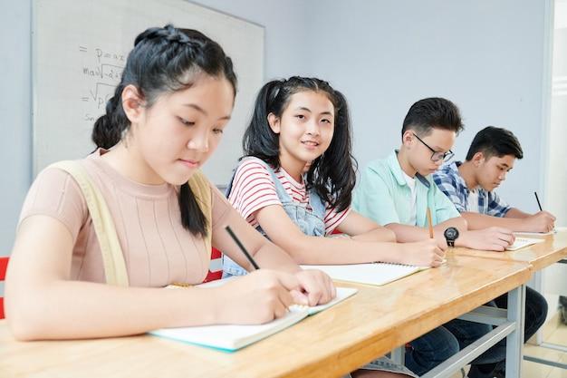 그녀의 급우가 수업 시간에 공부하고 카피 북에 쓰는 아시아 학교 학생
