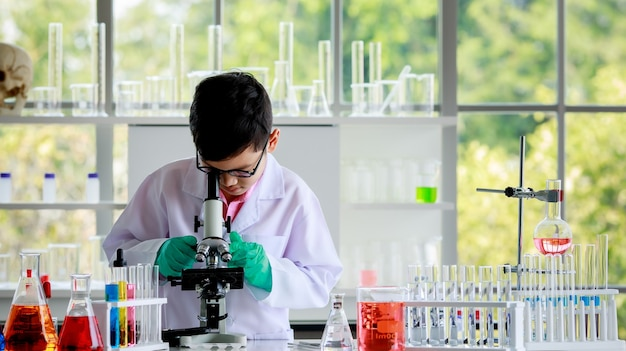 Asian schoolboy in glasses and lab coat examining chemical substance through microscope while conducting scientific experiment in school laboratory.