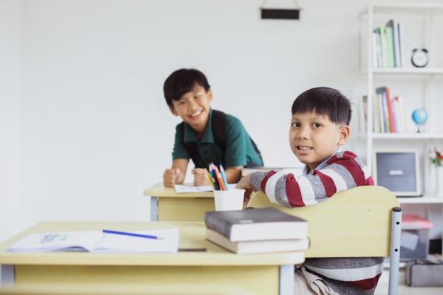 教室でポーズをとってカメラを見ているアジアの男子生徒