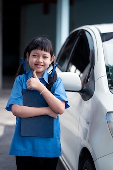 Asian schoolgirl holding a book with standing side of the car. back to school concept