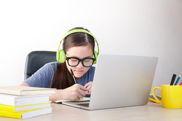 アジアの女子高生は、ビデオ通話を通じて自宅からオンラインで学びます。ラップトップコンピューターを使用して教師と通信する。オンライン教育の概念。コロナウイルスの蔓延を減らすための社会的距離。