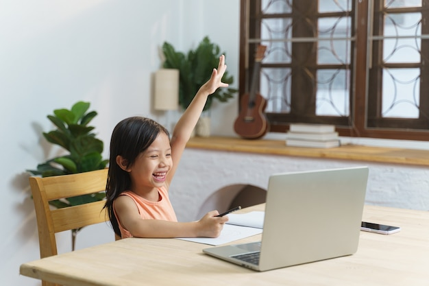 Asian schoolgirl student study and learning virtual online class by virtual video call using laptop