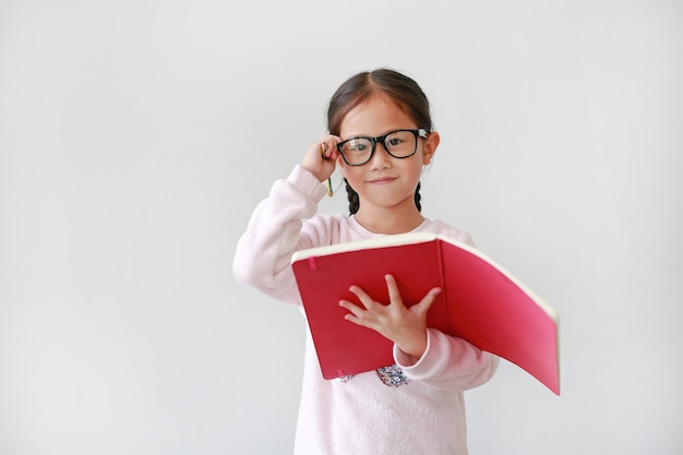 Asian schoolgirl wearing eyeglasses and holding notebook with pencil on white.