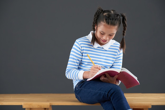Asian schoolgirl with braids sitting on table and writing in notebook